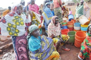 Bibi Mwanahawa (forground-seated) cuts a forlorn figure as she and her colleagues queue for the precious liquid at the water tap.
